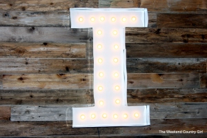 giant marquee letter on reclaimed wood wall